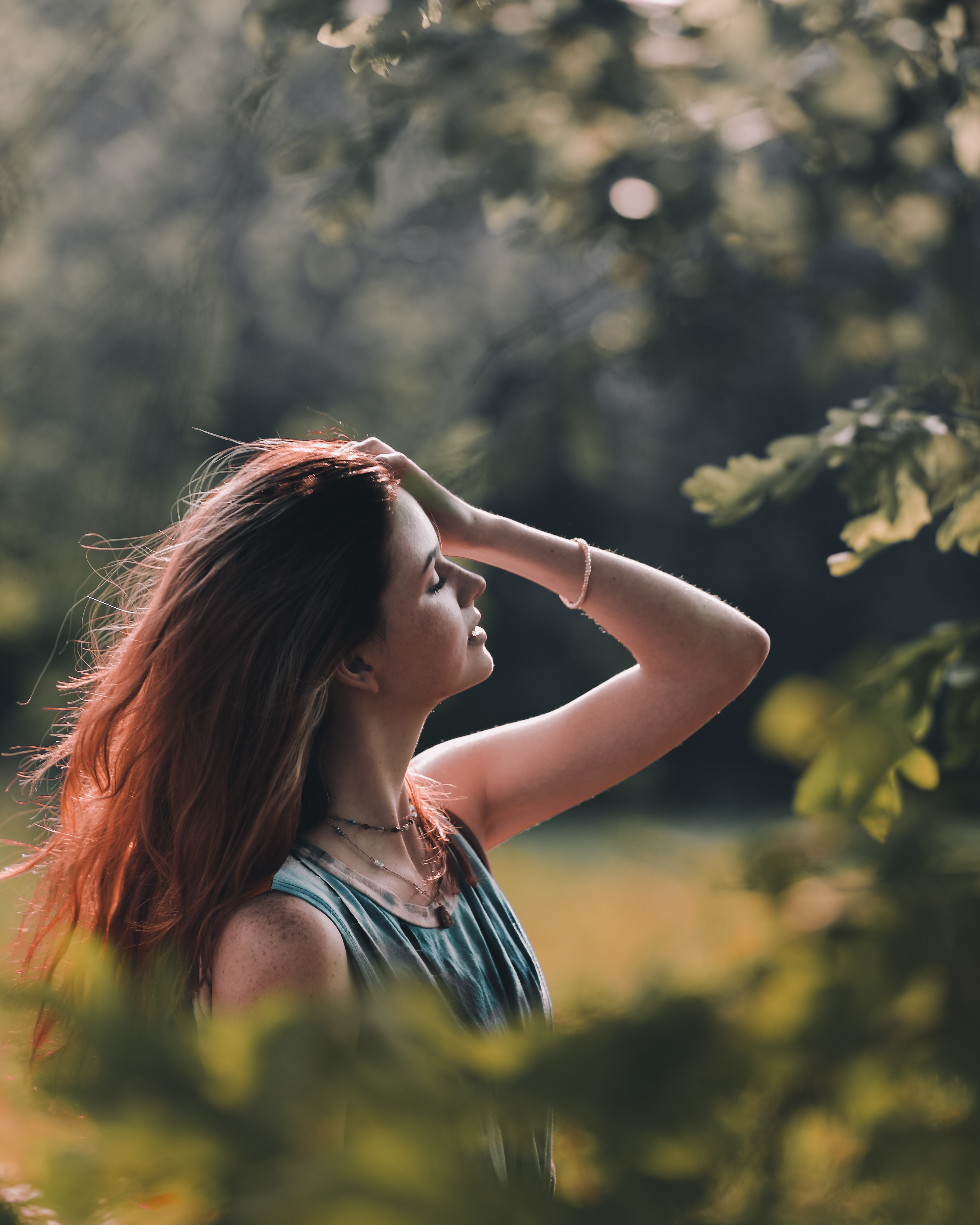 selective focus photography of woman holding her hair standing near trees