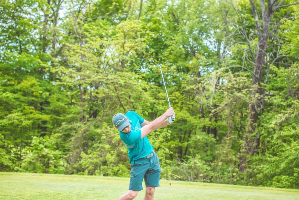 man playing golf near green trees during daytime