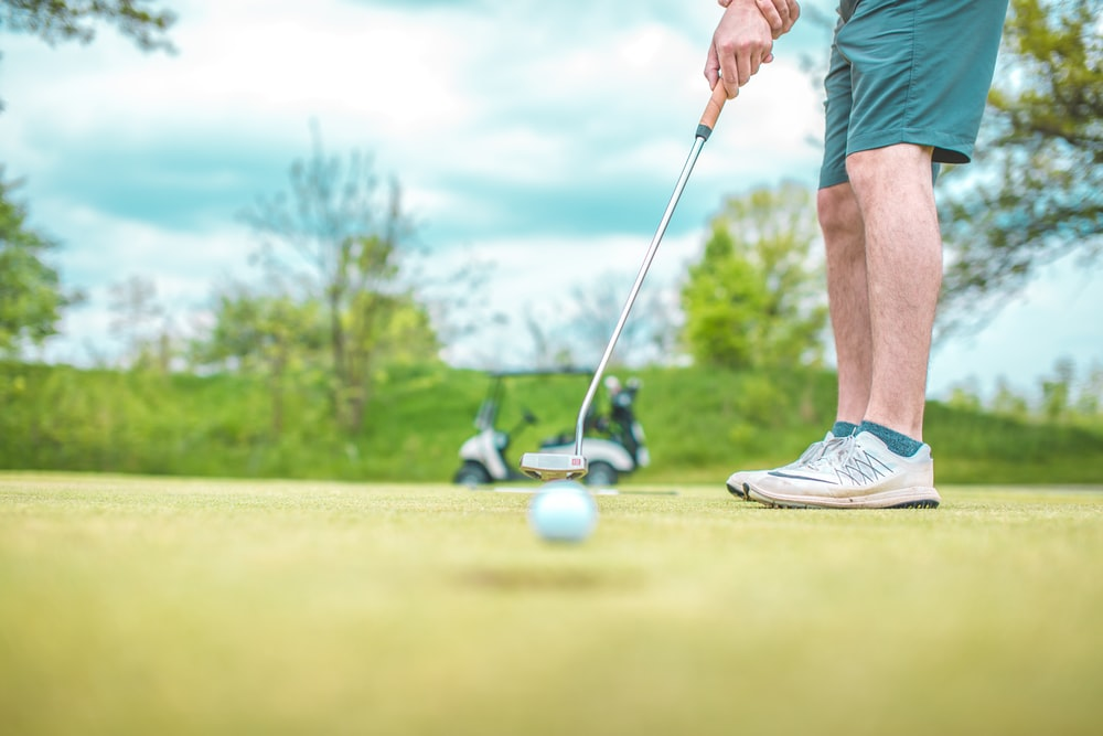 man playing golf under blue sky during daytime