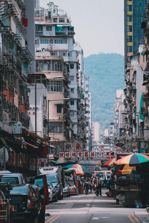 people walking between high rise buildings near mountain at daytime