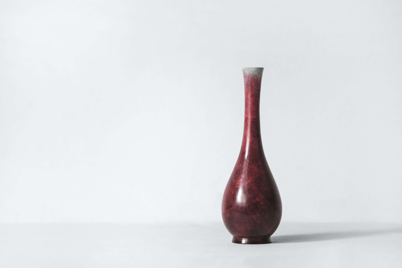 red ceramic vase on white surface
