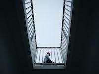 person sitting beside gray steel handrails