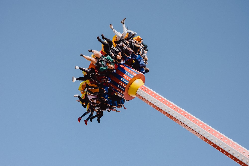 people riding carnival ride under clear blue sky during daytime