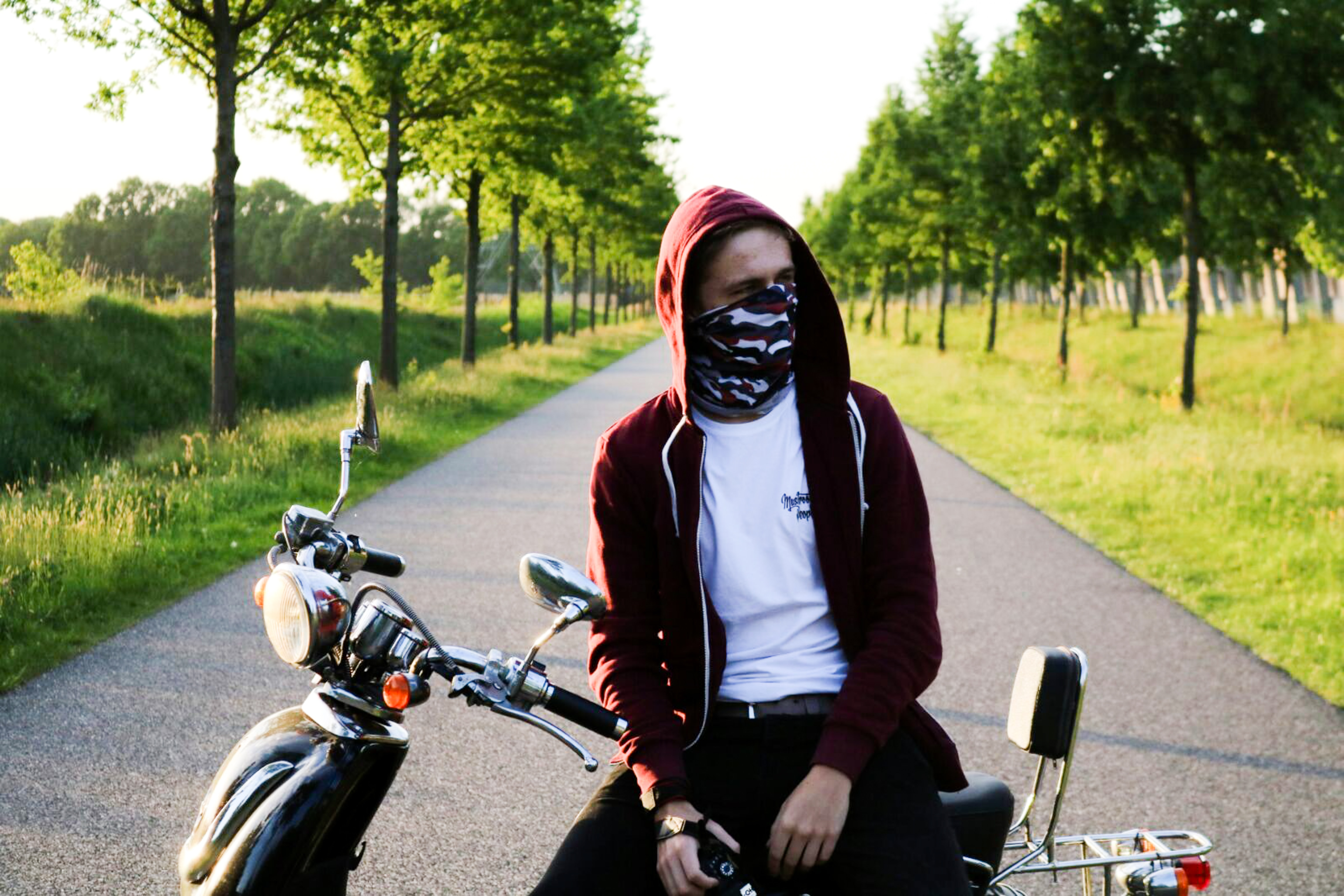 man covering his face with bandanna sitting on motorcycle