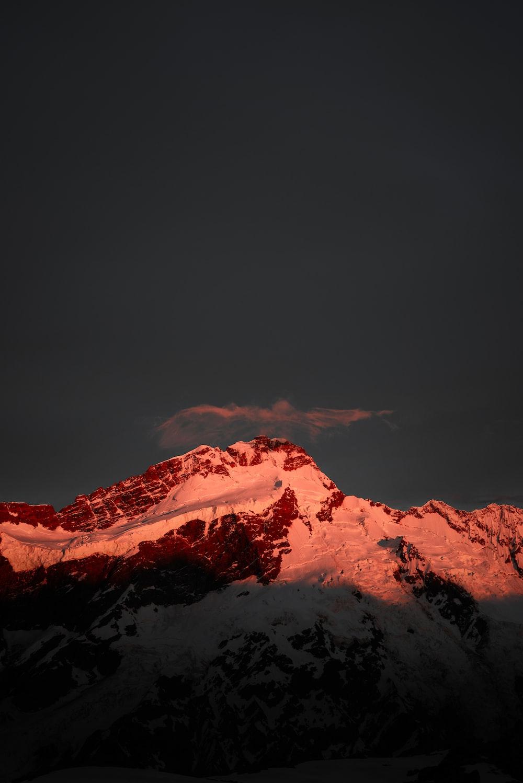 mountain covered in snow under dark sky