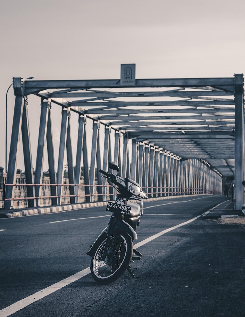 black motorcycle parked on bridge during daytime