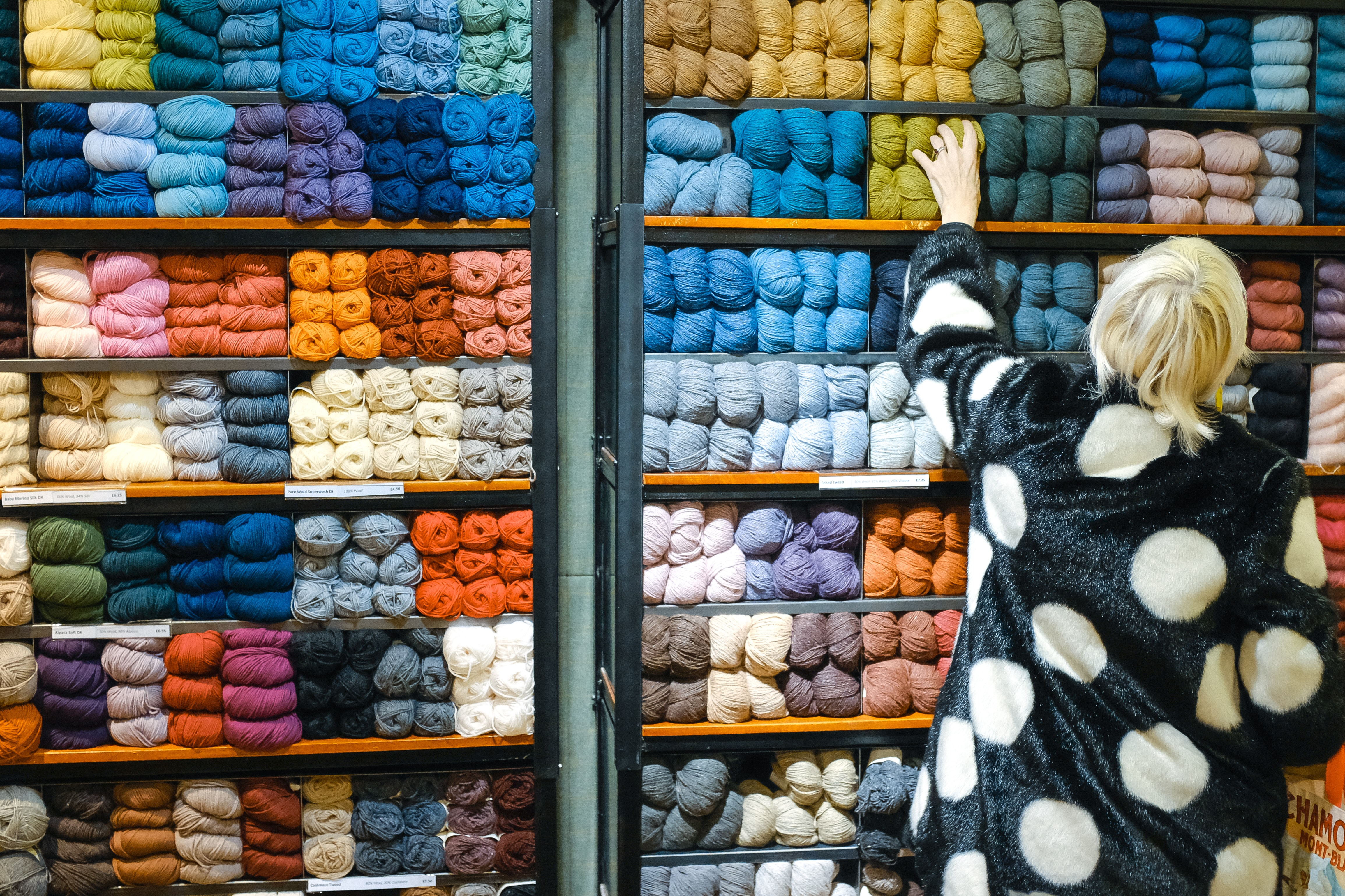 woman standing in front of displayed yarn rolls