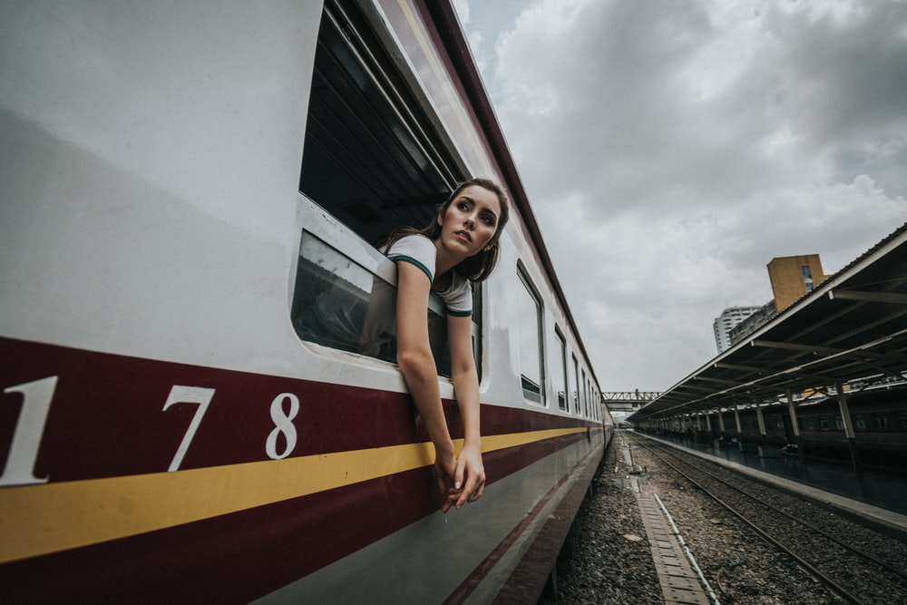 woman's head and hands outside train under cloudy sky during daytime