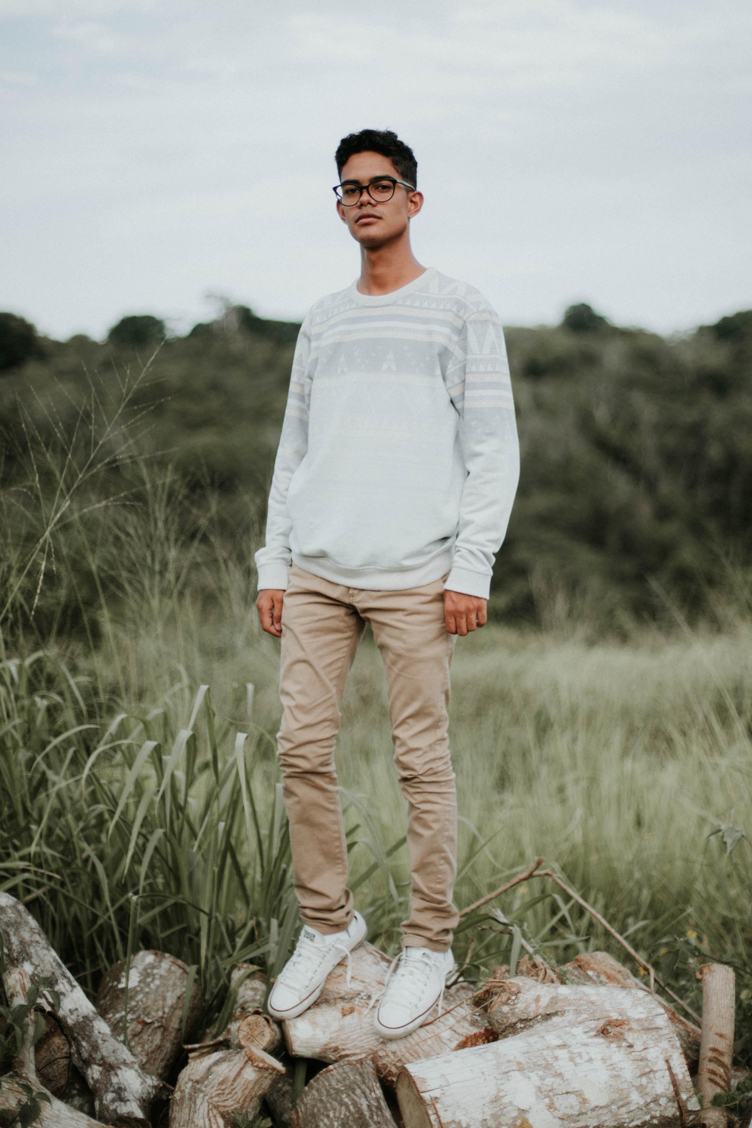 man standing wood logs