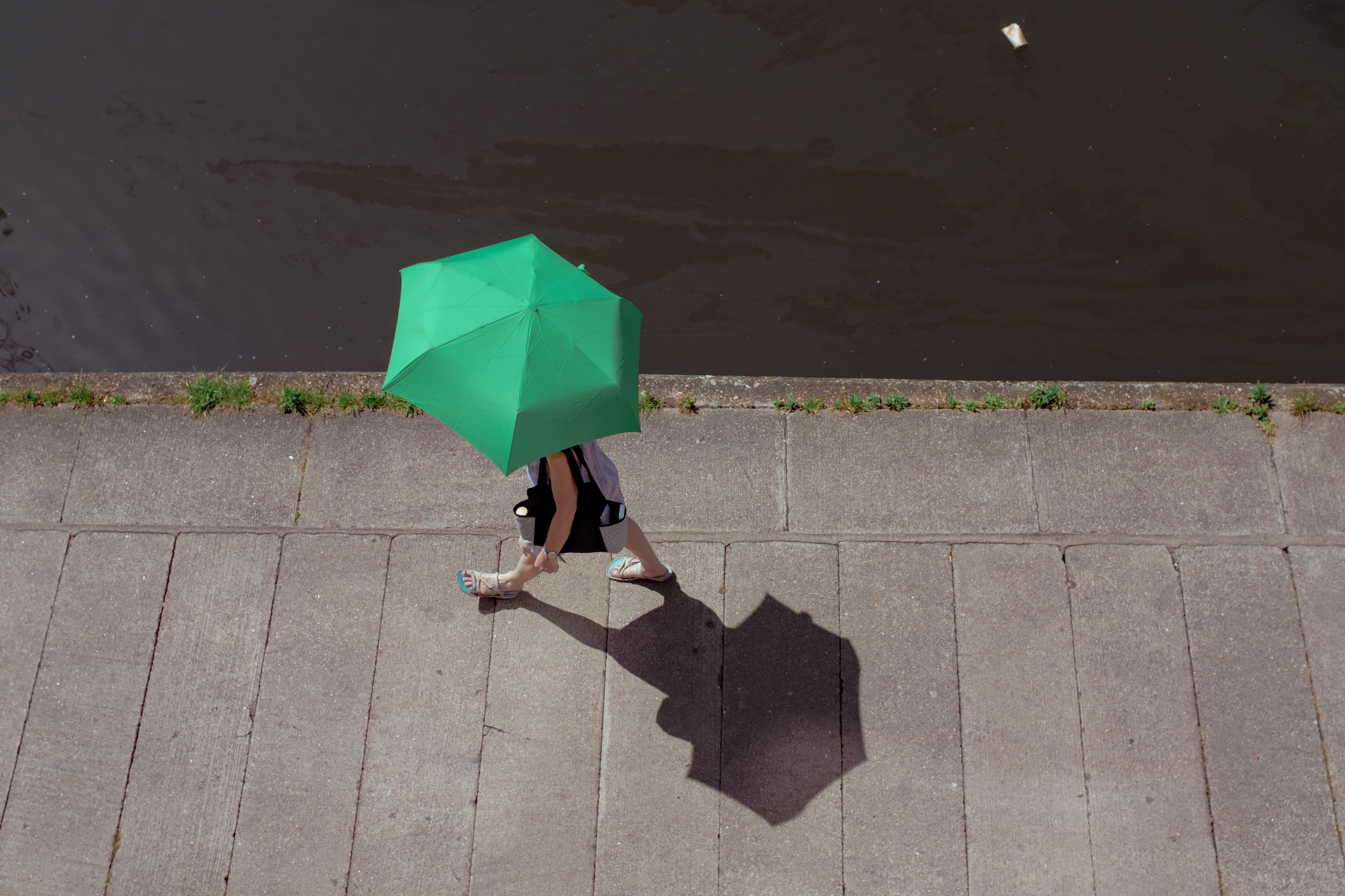 woman walking on grey pavement holding green umbrella