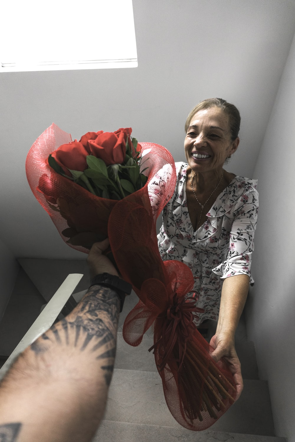 smiling woman receiving bouquet of red roses