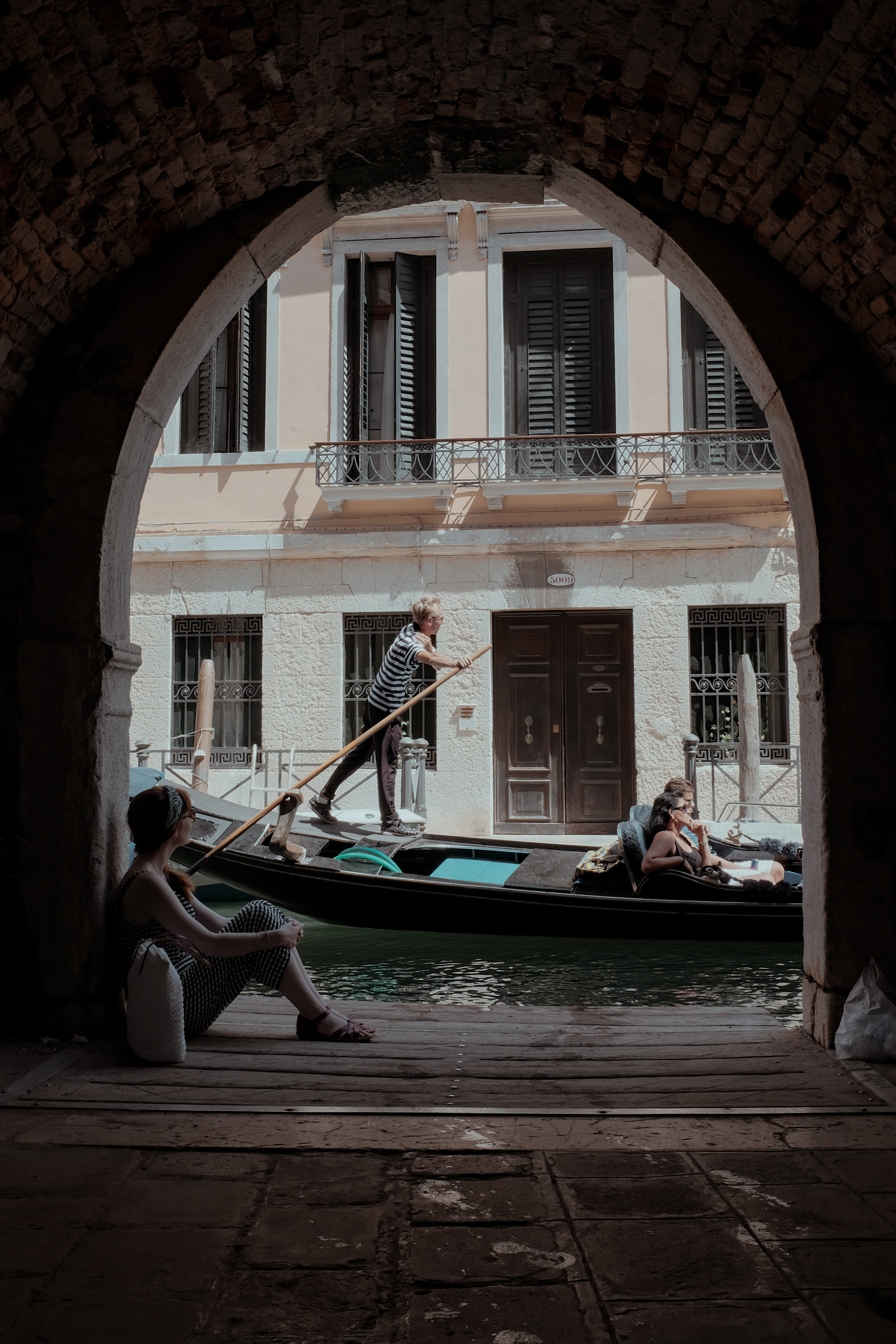 person rowing on gondola boat in Venice Canal