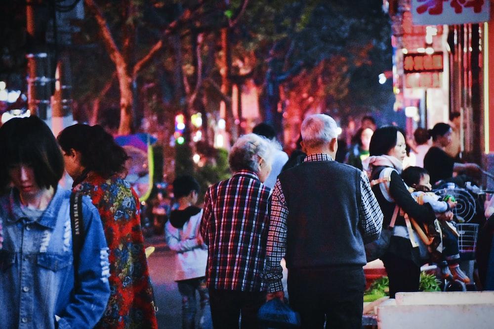 people walking on road near buildings during night