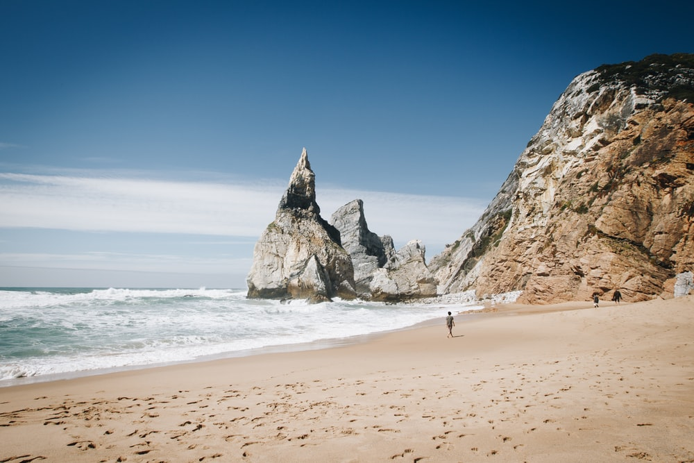 person walking on seashore near coastal stones