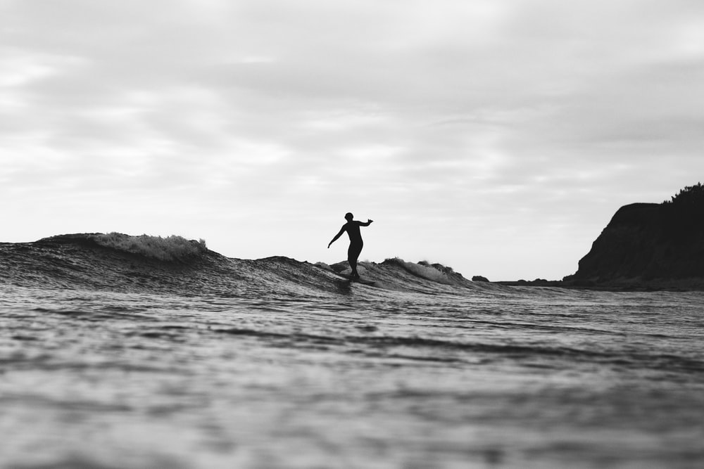 grayscale photography of person surfing on sea