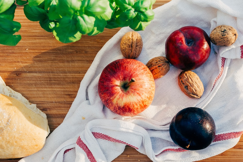 two apples and walnuts on white towel
