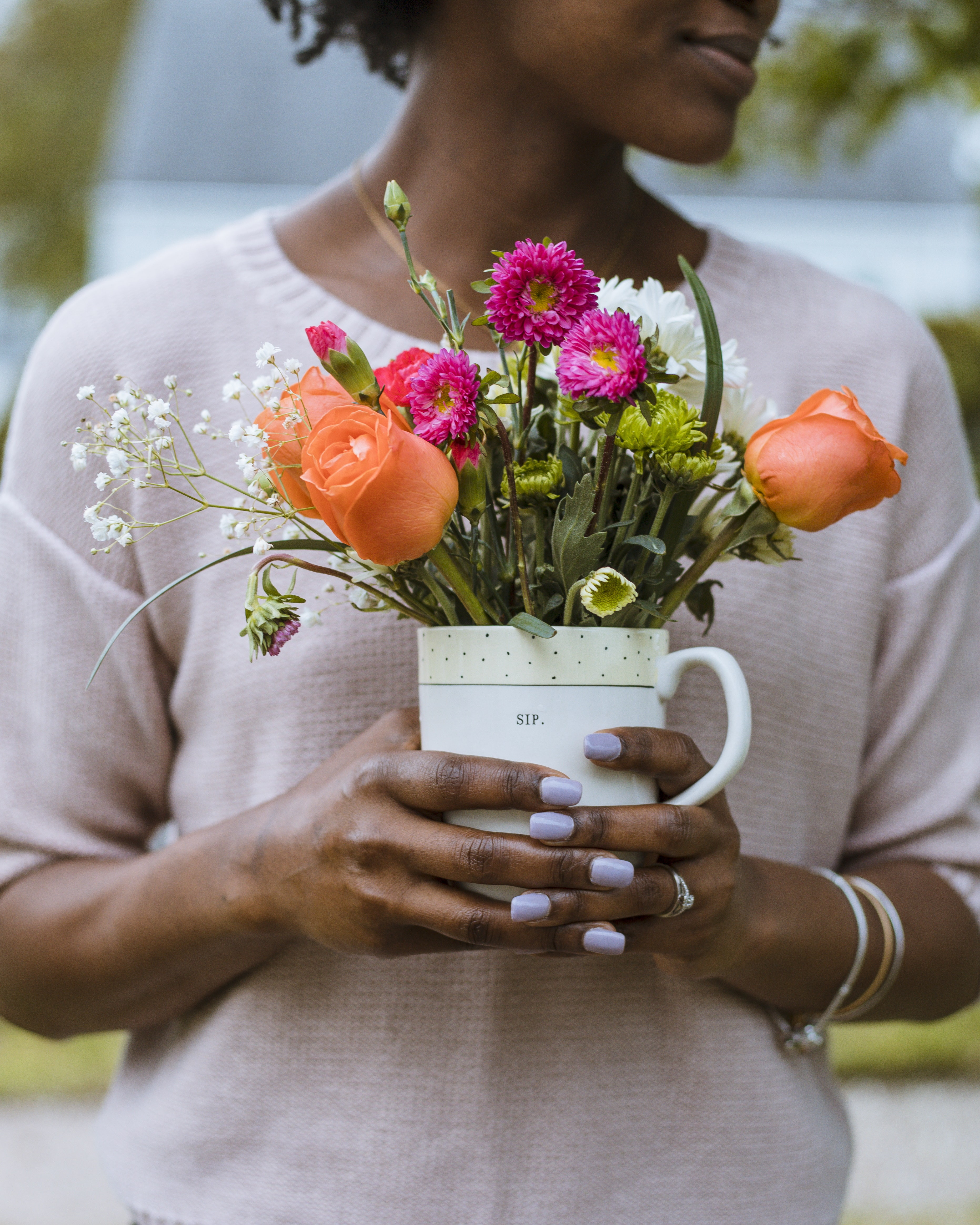 person holding pot of orange, pink, and white petaled flowerse