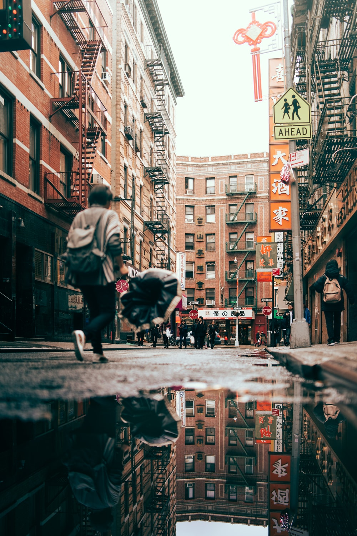 man walking near brown concrete buildings