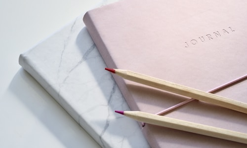 red and purple coloring pencils on pink journal