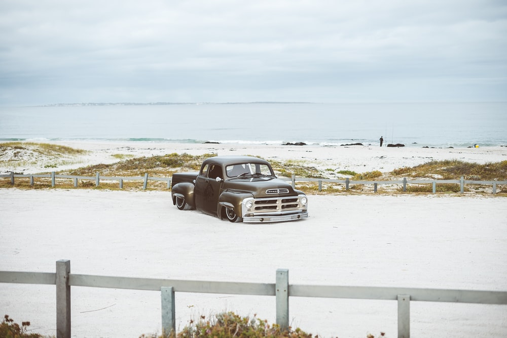 vintage brown pick-up truck near sea shore