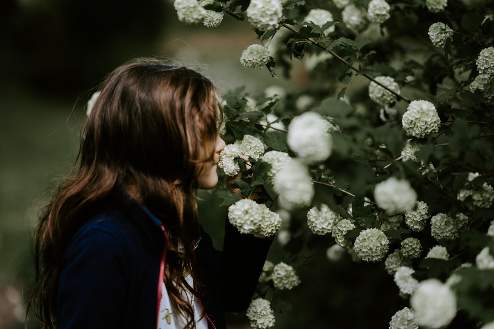 woman holding white flowers while facing sideway