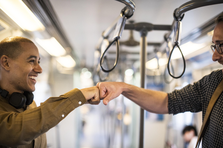 person fist bumping inside a train