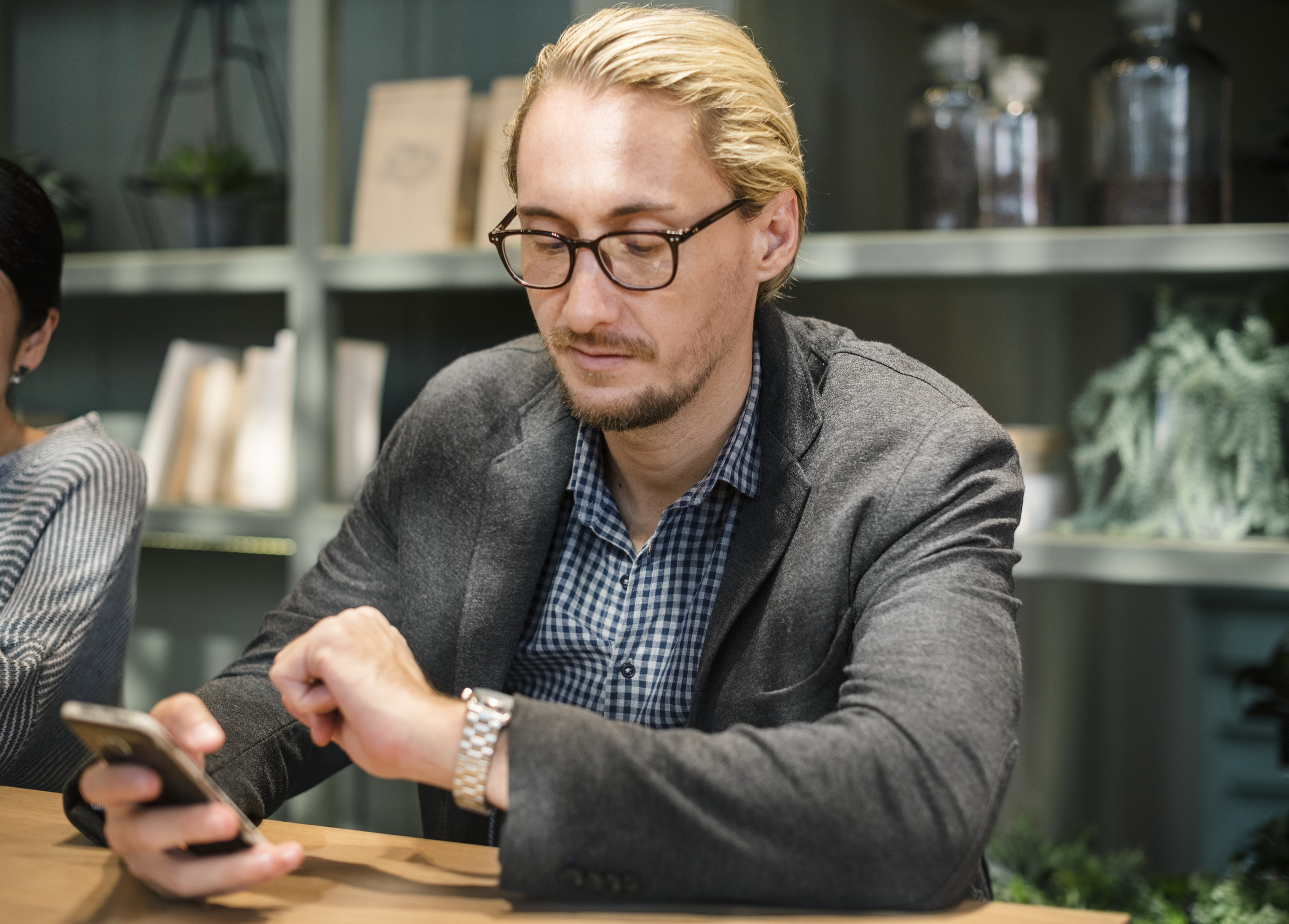 man looking at round silver-colored watch with steel link strap