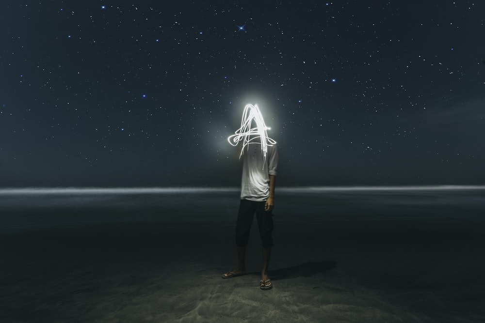 man standing on seashore at night