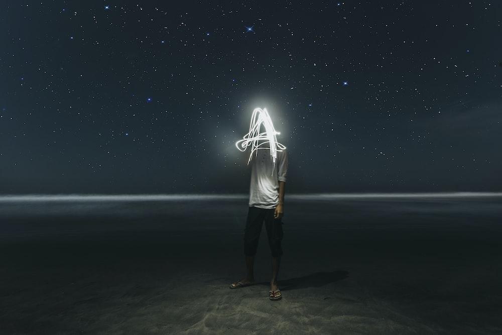 man standing on seashore at night