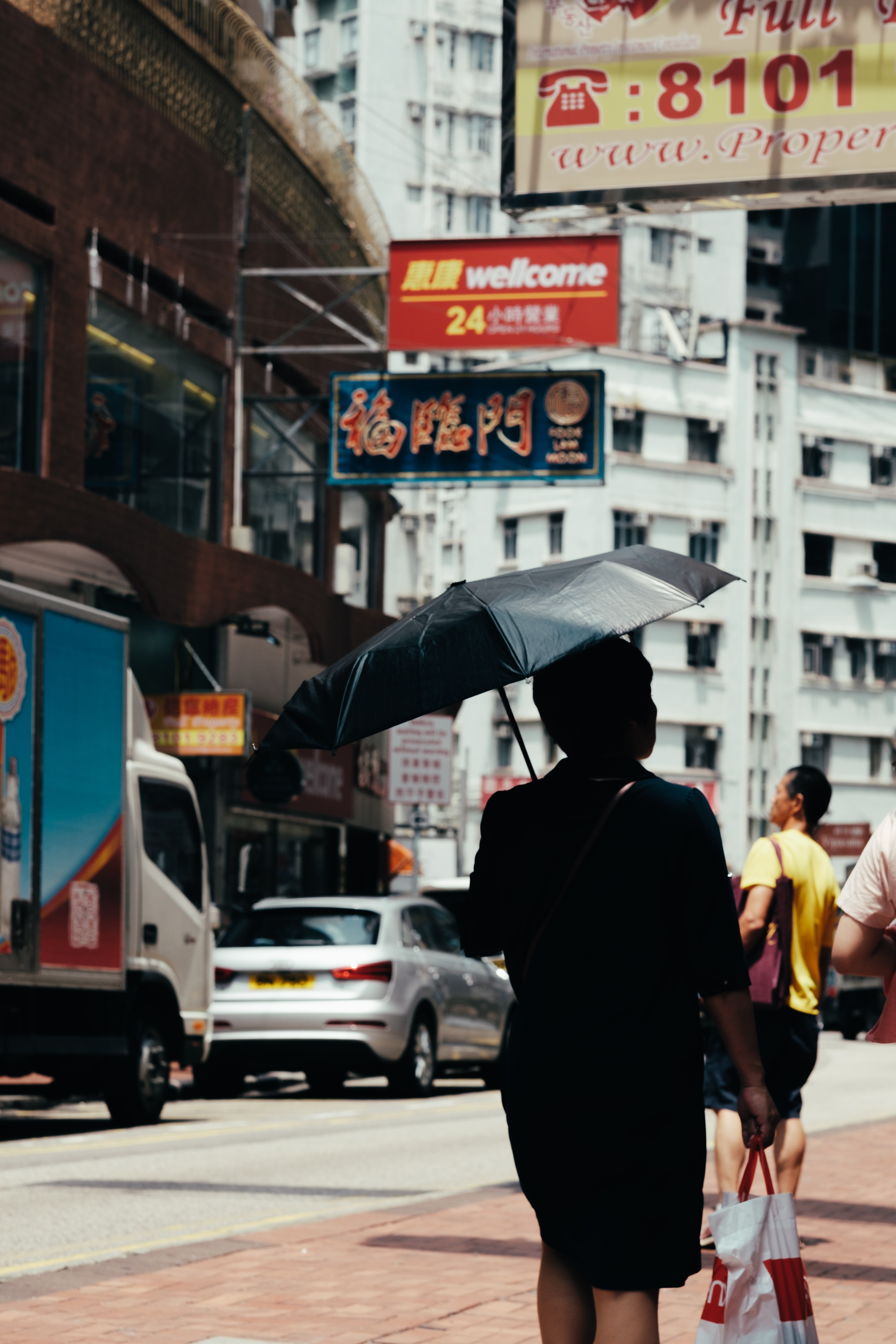 person holding umbrella walking on street