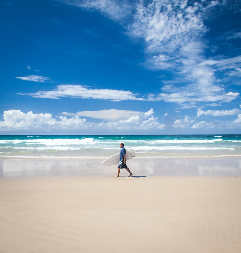man carrying his surfboard while walking on beach