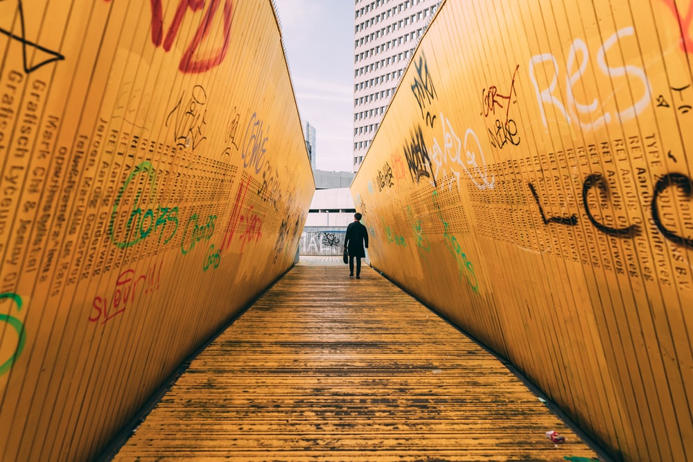 person standing on pathway between yellow wall with graffiti