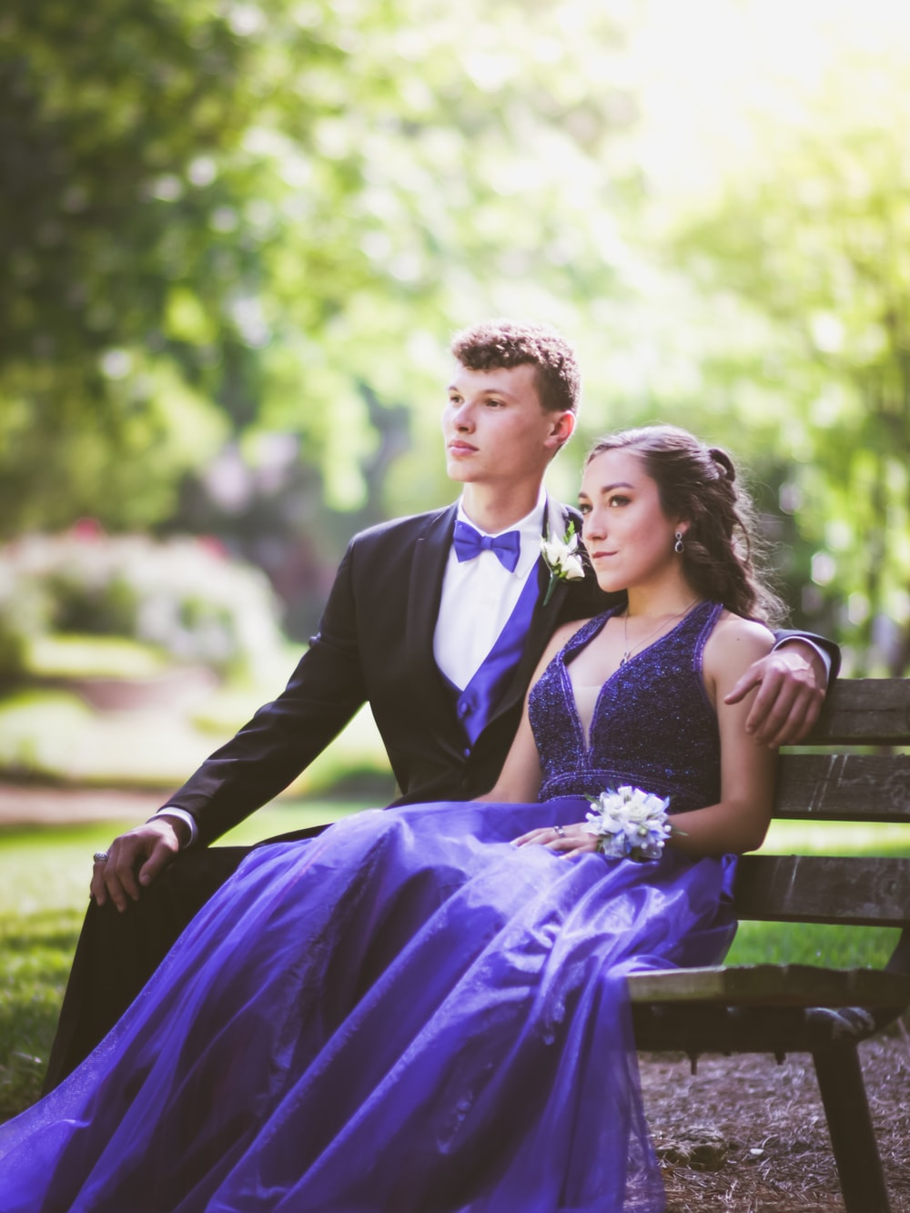 woman in purple sleeveless dress sitting on bench beside man in black suit