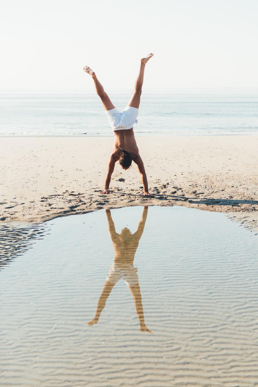 person doing cartwheel on seashore