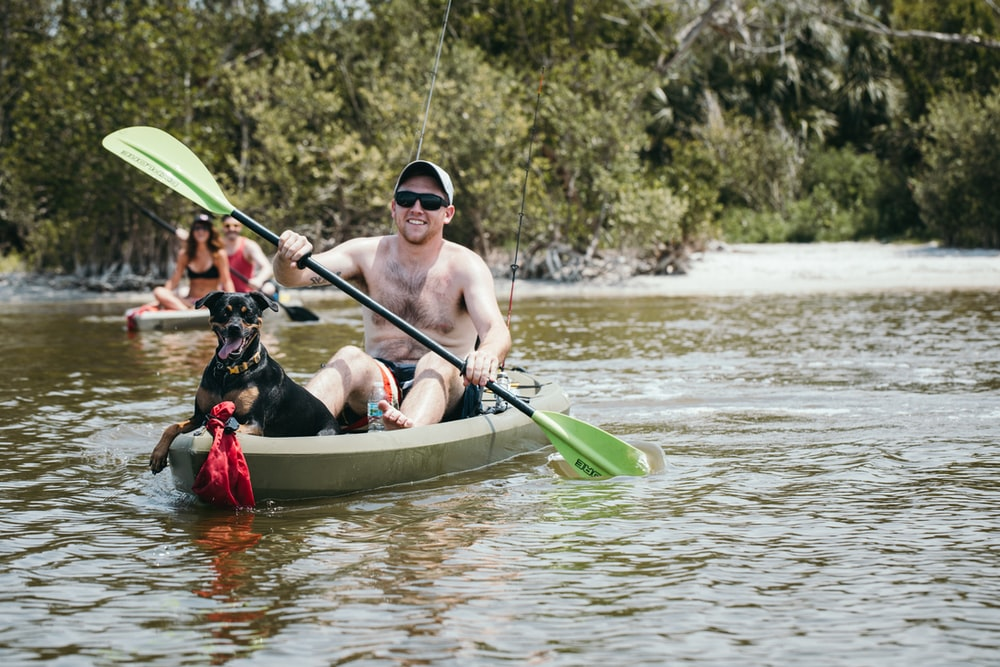 man kayaking with dog