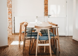 rectangular white wooden table and chairs in white wall paint room