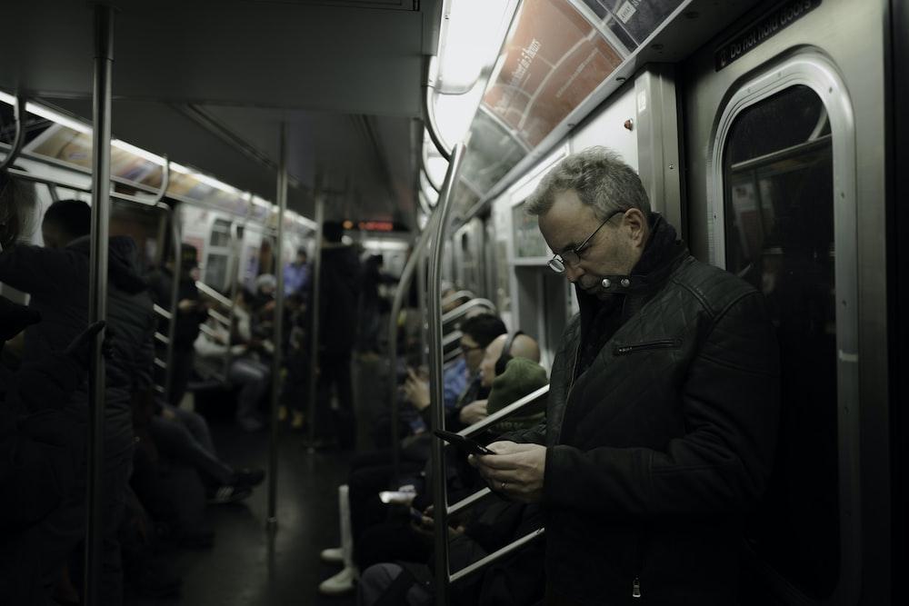man in gray coat standing near train door