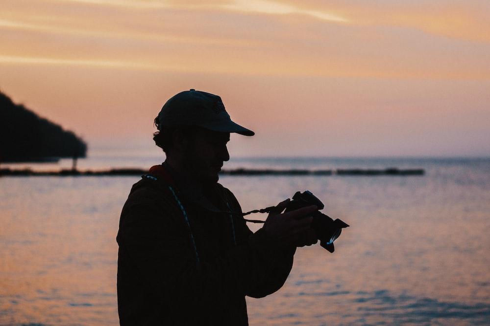 man doing photography using DSLR camera near body of water