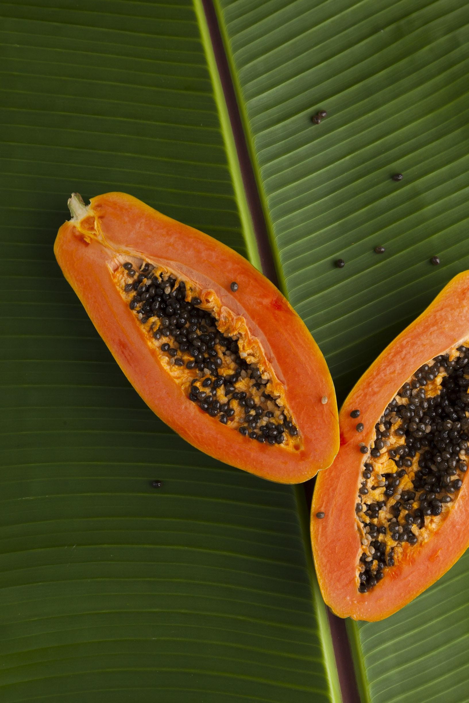 sliced papaya on green banana leaf