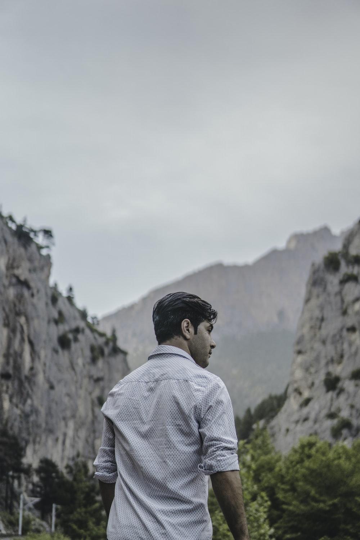 man facing rock formation at daytime