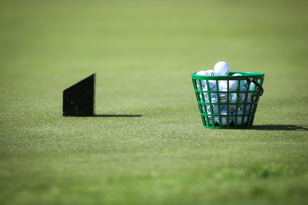 basket of golf balls on green grass
