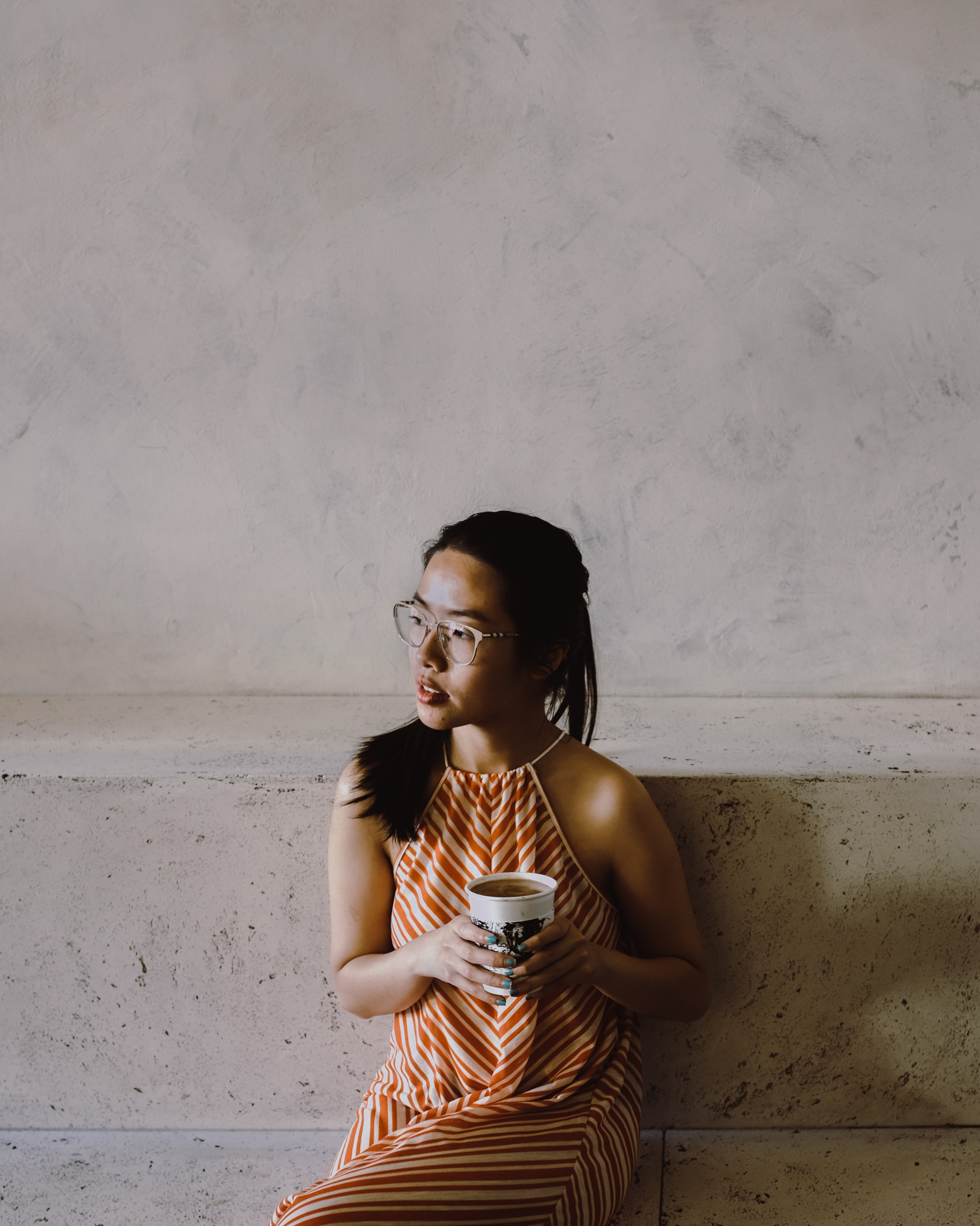 woman sitting while holding white coffee cup