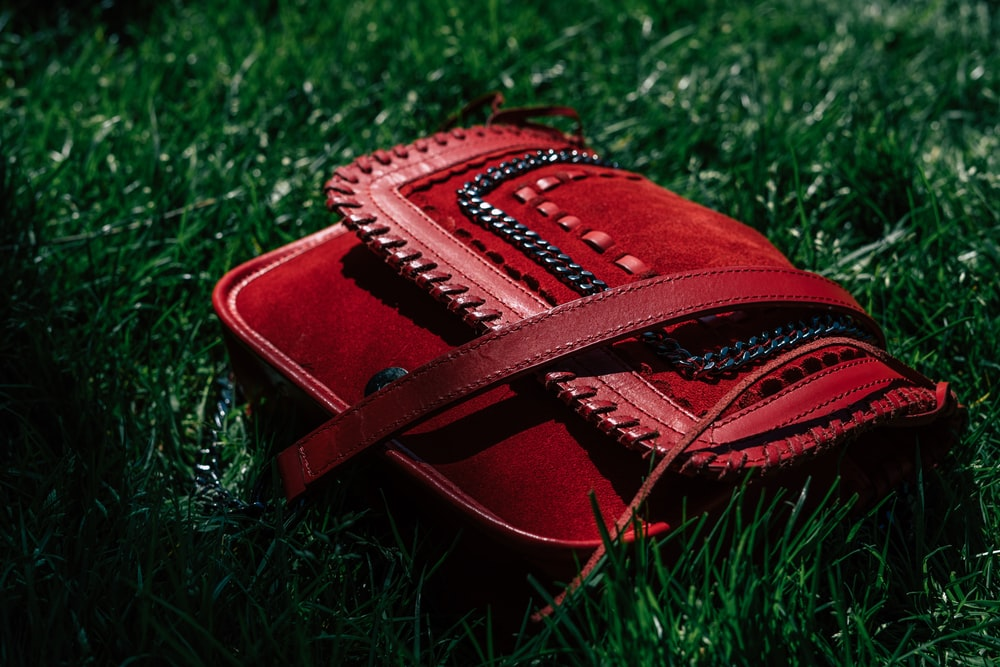 red leather handbag on grasses