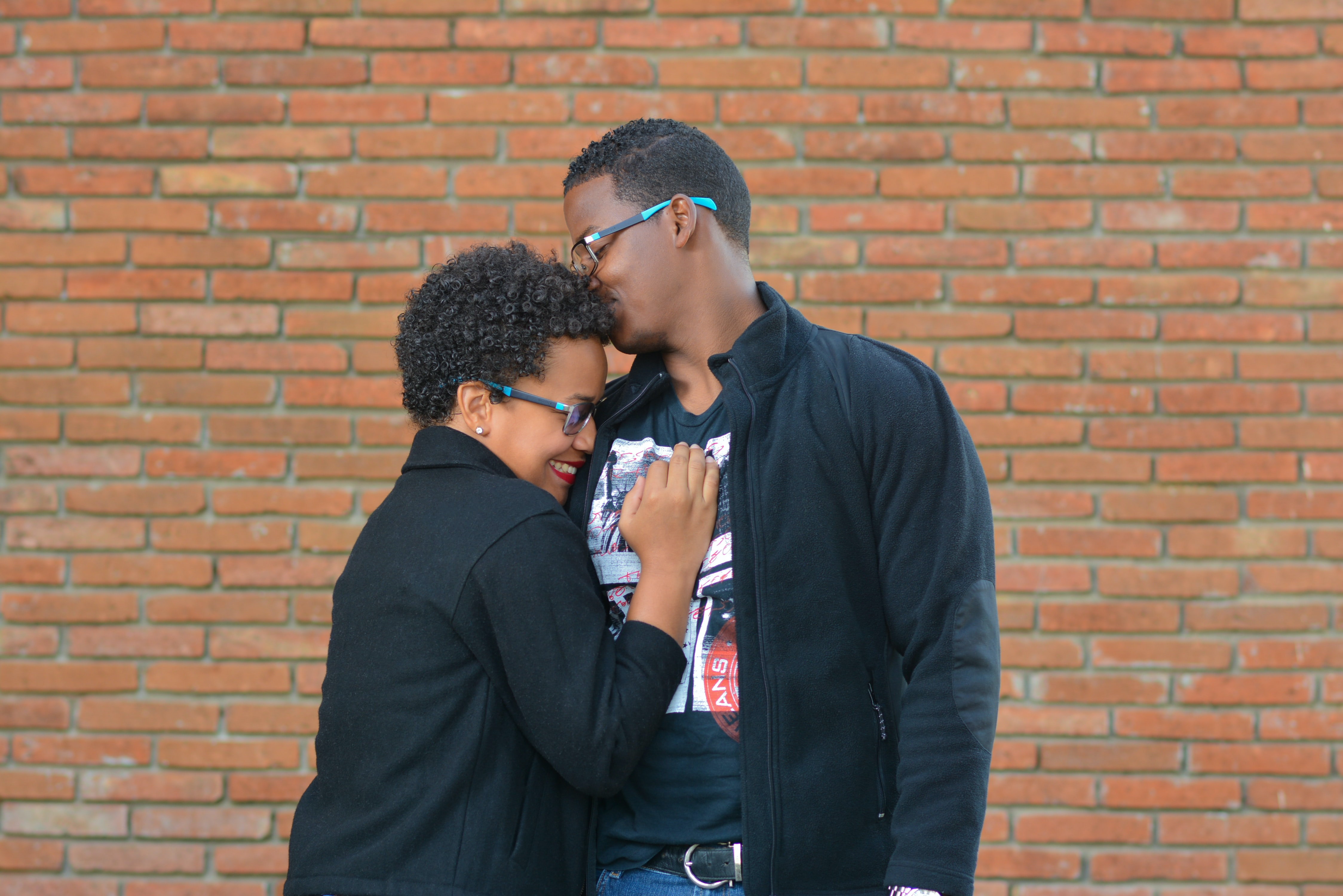 man kissing the forehead of woman