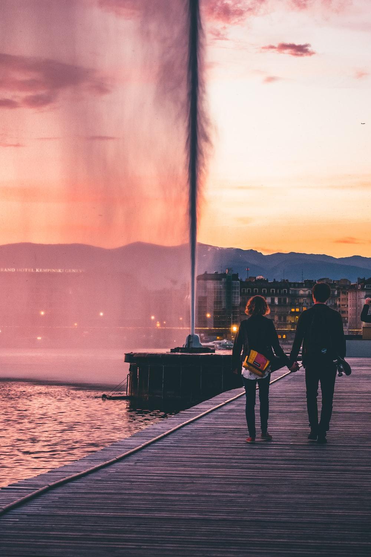 couple walking on wooden bridge near body of water