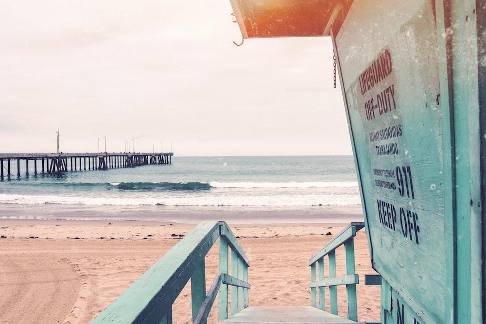 teal wooden lifeguard shed near seashore