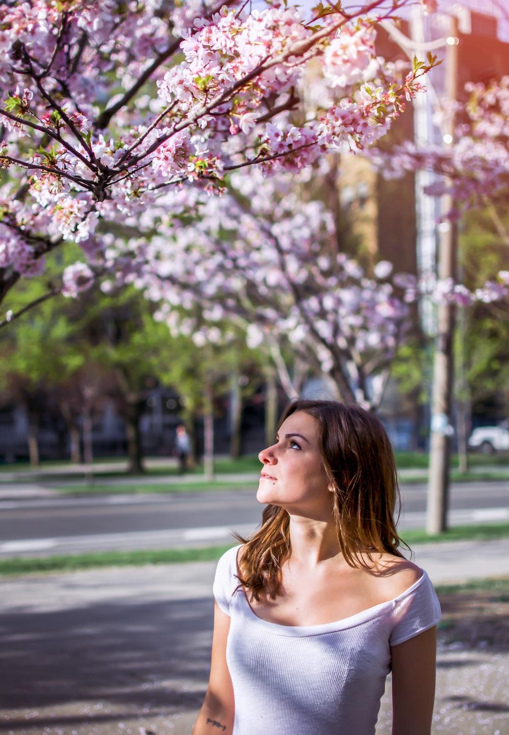 woman wearing pink top looking at pink flowering tree