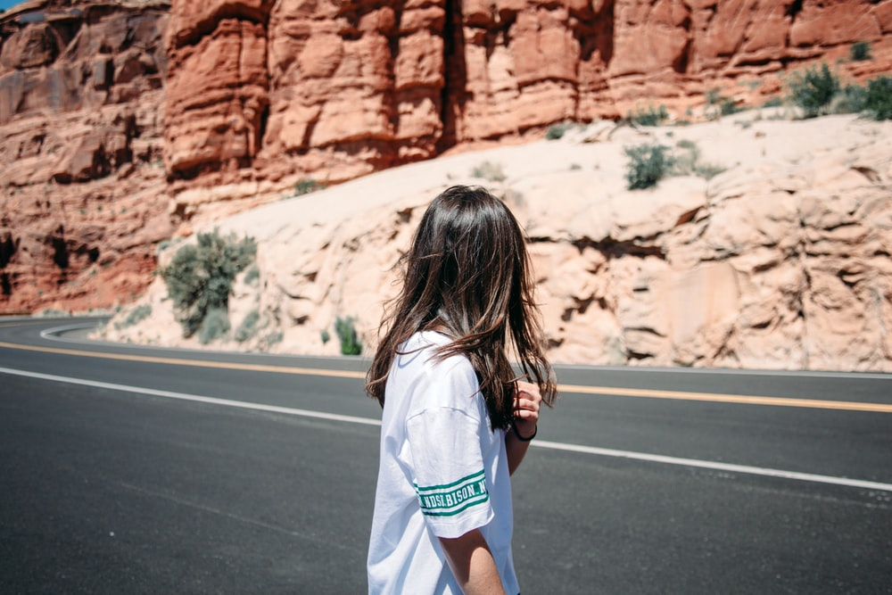 woman standing beside the road during daytime