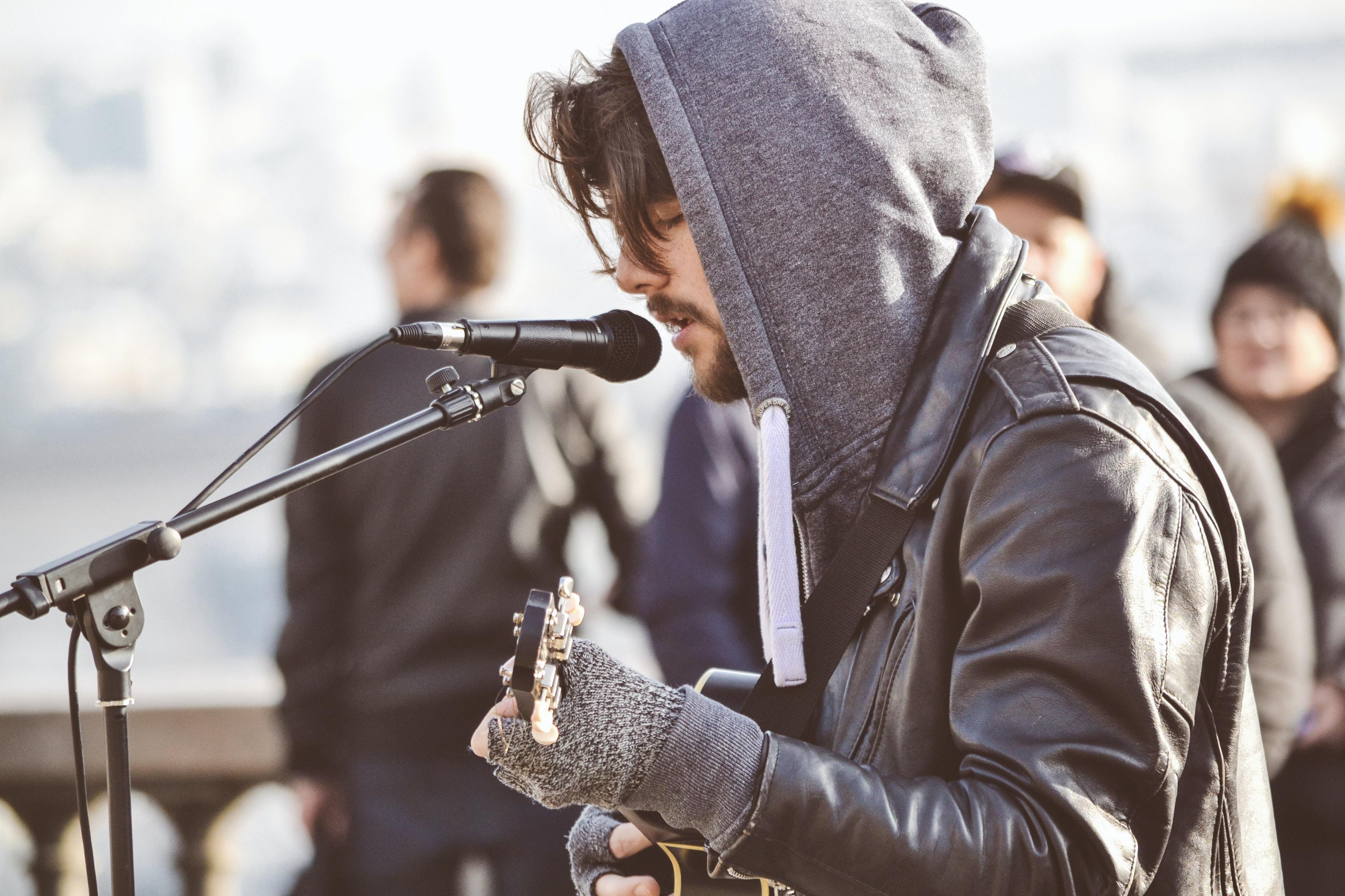 man facing sideways playing guitar