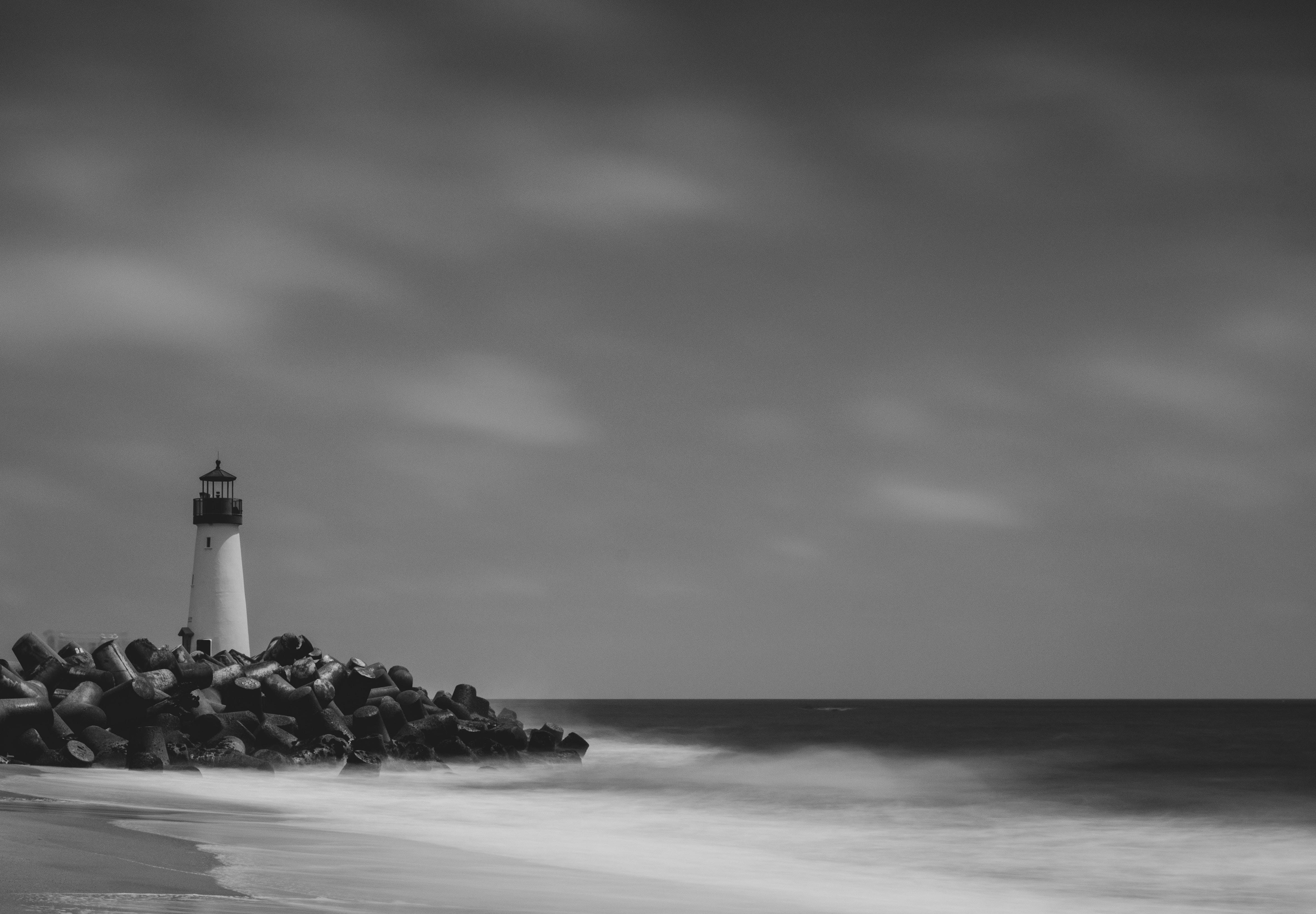 greyscale photo of lighthouse near shore